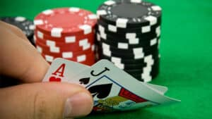 Hand at Casino Table with Cards and Chips