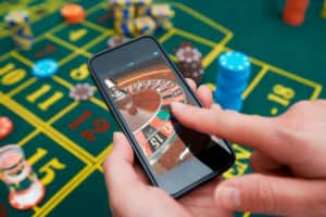 Gambling Game on Smartphone Screen with Roulette Layout in Background
