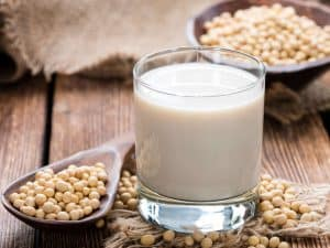 Glass of Vanilla Soymilk Surrounded by Soybeans