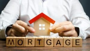 "Man Placing Small House on Top of Blocks Spelling ""Mortgage"""