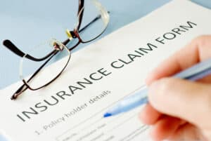 Insurance Claim Form and Hand with Pen