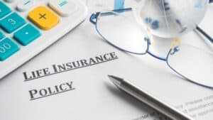 Life Insurance Policy Papers on Desk with Other Items