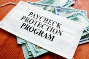 "Pile of Money with Mask Saying ""Paycheck Protection Program"" on Top"