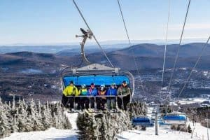 Six People Riding Ski Lift Up Mountain