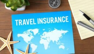 """Words """"Travel Insurance"""" on Paper with Compass and Two Starfish"""