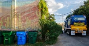 Waste Connections Truck in Alley with Trash Containers