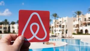 Hand Holding Up Card with Airbnb Logo in Front of Resort
