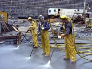 Three workers in protective gear performing industrial cleaning