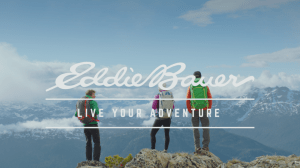 Eddie Bauer Ad with Three People on Peak Looking at Distant Mountains