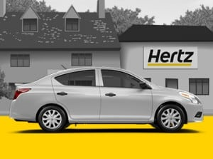 Car in Front of Hertz Office: Black-and-White Image with Yellow Details