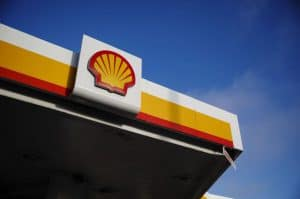 Shell Logo Attached to Gas Station Roof Against Blue Sky