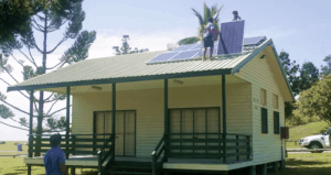 Small House with Two Workers on Roof, Installing Solar Panels