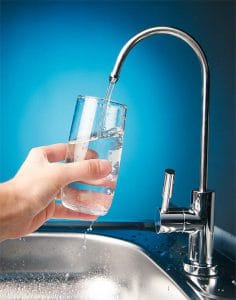 Hand Holding Glass Under Tap for Drinking Water