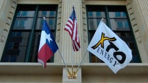 Texas Flag, American Flag, and XTO Flag Flying from Front of Building